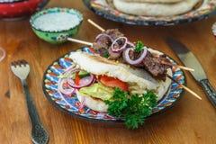Souvlaki или kebab, зажаренный протыкальник мяса и провозглашанный тост хлеб стоковая фотография