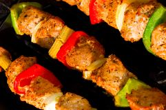 Souvlaki. Three diagonally shot metal skewers with meat, onions, red and green peppers making souvlaki Royalty Free Stock Image