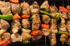 Souvlaki. Eight bamboo skewers with meat, onions, red and green peppers and corn making souvlaki Royalty Free Stock Photos