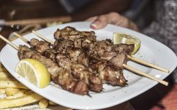 Souvlaki greek etnic food mear roasted in a plate with lemon royalty free stock image