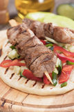 Souvlaki or kebab on pita bread. Souvlaki or kebab with vegetable salad on pita bread Stock Image