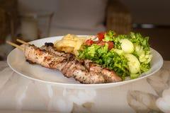 Souvlaki with salad and fried potatos. Royalty Free Stock Image