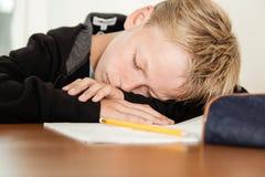 Sova barnet med huvudet på armar bredvid läxa Arkivfoto