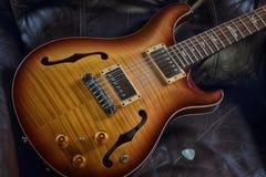 Sova den halva hollowbody akustiska elektriska gitarren för skönhet`-tappning i läderstol Royaltyfria Bilder