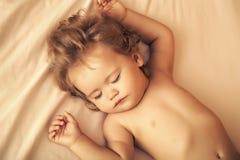 sova för barn Älskvärt litet sova pojkebarn med blont lockigt hår Arkivbild