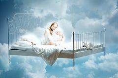 sova kvinna Flicka med en kudde och en filt på sängen bland Fotografering för Bildbyråer
