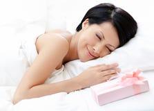 Sova kvinna och gåva på sängen Royaltyfri Bild