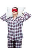 Sova kvinnan på en kudde i plädpyjamas med en maskering Arkivbilder