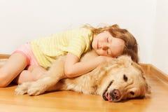 Sova lilla flickan som ligger på hennes golden retriever Fotografering för Bildbyråer