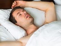 Sova mannen i säng med hans arm upp royaltyfri bild