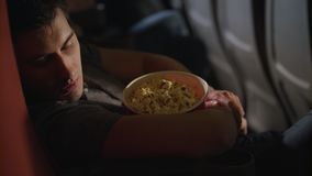 Sova mannen som omfamnar popcornasken på bion Grabb som sover i stol på bion arkivfilmer