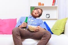 Sova på ett parti med popcorn och öl Royaltyfri Fotografi