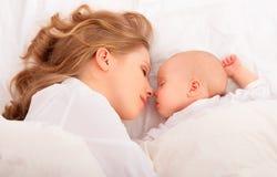 Sova tillsammans. fostra omfamningar som det nyfött behandla som ett barn i säng Royaltyfri Bild