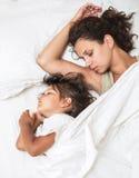 Sova ungeflickan och hennes moder i en säng royaltyfri fotografi