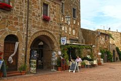Tourists relax in outdoor cafe on central square of Sovana, Tuscany, Italy stock images