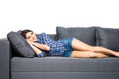 Sovande faller kvinnan som sover på en grå soffa som isoleras på vit bakgrund arkivbild
