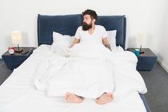 sovande och vaket F?r tidigt att vakna upp sk?ggig manhipsters?mn i morgon mogen man med sk?gget i pajama p? s?ng royaltyfria foton