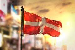 Sovereign Military Order of Malta Flag Against City Blurred Back. Ground At Sunrise Backlight Sky Royalty Free Stock Photo