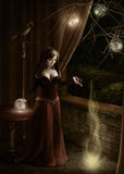 Sovereign of souls. Young woman in a dark room, dropping and breaking up a magic ball Royalty Free Stock Images