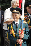 Soviet Army veteran with flag. SLAVIANSK, UKRAINE - MAY 9, 2012: MAY 9: Unidentified Soviet Army veteran of World War II with flag on Victory day in Slaviansk on Royalty Free Stock Photo
