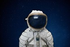 Soviet cosmonaut or astronaut or spaceman suit and helmet on black space with stars background stock photo