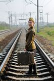 Soviet female soldier with a suitcase in the uniform of the Second World War standing on the train tracks. Soviet female soldier with a suitcase in the uniform Royalty Free Stock Photos