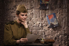 Soviet female soldier in uniform of World War II reads the lette Royalty Free Stock Photography