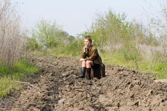 Soviet female soldier in uniform of World War II siting on a suitcase on a plowed road. Soviet female soldier in uniform of World War II sits on a suitcase on a Royalty Free Stock Photo