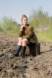 Soviet female soldier in uniform of World War II siting on a suitcase on a plowed road. Soviet female soldier in uniform of World War II sits on a suitcase on a Stock Image