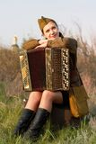Soviet female soldier in uniform of World War II sits with an accordion on a suitcase. Pretty Soviet female soldier in uniform of World War II sits with an Stock Photos