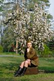 Soviet female soldier in uniform of World War II sits on a suitcase near flowering tree. Pretty Soviet female soldier in uniform of World War II sits on a Royalty Free Stock Photo