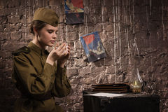 Soviet female soldier in uniform of WWII in the dugout. Soviet female soldier in uniform of World War II in the dugout royalty free stock photos