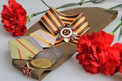 Soviet military cap with red flowers, Saint George ribbon, medals of Great Patriotic war Royalty Free Stock Photos