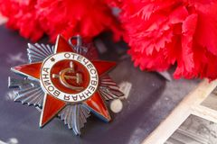Soviet order of Patriotic war inscription Patriotic war with red carnations against the background of old photos. May 9 Victory royalty free stock photos