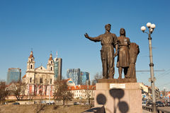 Soviet realism sculpture and a church, Vilnius. Stock Photos