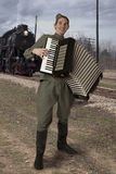 Soviet soldier with an accordion outdoors. Soviet soldier dressed in uniform of World War II playing the accordion outdoors royalty free stock photo