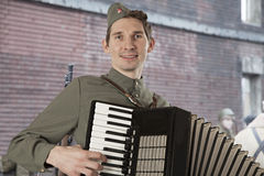 Soviet soldier playing the accordion outdoors. Portrait of Soviet soldier in uniform of World War II playing the accordion outdoors stock photography