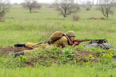 Soviet soldier of WW2 shooting in the field Stock Images