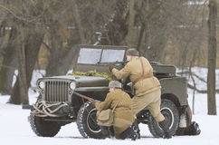 Soviet soldiers hiding behind a jeep Willys, shooting the enemies. Royalty Free Stock Photography