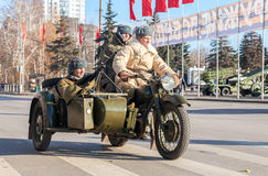 Soviet soldiers with weapons on the old army motorcycle Stock Photography