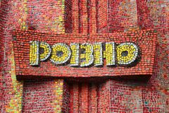 Soviet style wall mosaic in Rovno, Ukraine. Rivne, Ukraine - December 13, 2011: Soviet style wall mosaic with word `Rovno` in Russian, installed in 1983 to Stock Photos