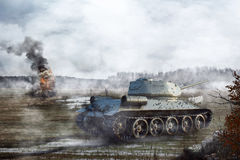 Soviet Tank goes through the swamp in the background of a burning tank stock photos