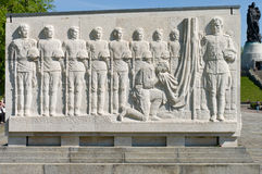 Soviet War Memorial (Treptower Park). The bas-relief, soldiers and an officer kneeling at the flag Royalty Free Stock Images