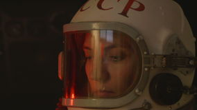 Soviet Woman Cosmonaut. Portrait of a russoan astronaut inside a space shuttle. On the helmet are painted with red letters the USSR or CCCP, THE Soviet Union stock footage