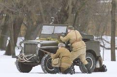 Sovjet tjäna som soldat nederlag bak en jeep Willys, skytte fienderna royaltyfri fotografi