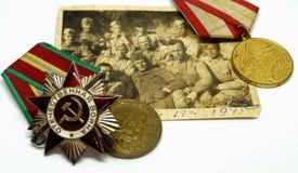 Sovjetbeställningar och medaljer ligger på ett gammalt militärt fotografi Arkivbild