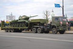 Sovjetisk behållare T-34-85 på den militära släpet Kamaz-65225 Arkivfoto