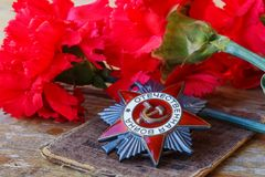 Sovjetisk beställning av det patriotiska kriget för patriotisk kriginskrift med röda nejlikor på en gammal trätabell Maj 9 dag av arkivbild
