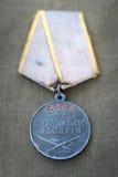 Sovjetisk medalj för stridservice och två röda nejlikor royaltyfri fotografi