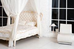 Sovrum i mjuka ljusa färger Stor bekväm dubbelsäng för fyra affisch i elegant klassiskt sovrum Lyxig elegant vit med guld in arkivbilder